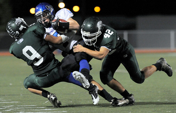 "Longmont High School junior D.J. Fowler gets tackled by Niwot senior Xandon Sigafoos, No. 9, and junior Nick Stager, No. 42, during a football game on Thursday, Oct. 8, at Longmont High School.<br /> For more photos go to  <a href=""http://www.dailycamera.com"">http://www.dailycamera.com</a><br /> Photo by Jeremy Papasso"