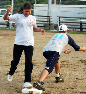 Angie Cortes, left, runs out a base hit by Little Lighthouse first baseman Joe Akosi in co-ed kickball league at Oakwood Park in Lorain Sep. 8.   Steve Manheim