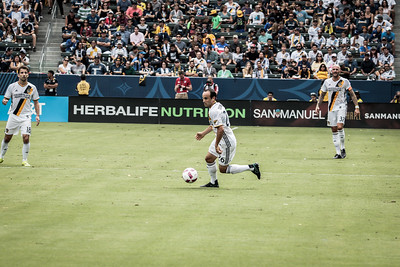 Landon Donovan makes a quick turn and moves the ball down field. Mike Magee (l) and Jelle Van Damme (r).
