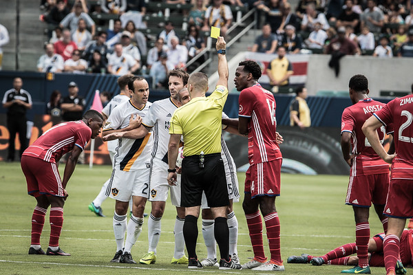 Landon Donovan gets a yellow card in the first half of the game. Mike Magee holds him back.