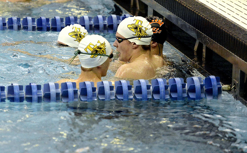 . Thompson Valley swimmers take a break at the wall during warmups for Friday\'s 4A state swimming preliminaries at the Air Force Natatorium.  (Photo by Mike Brohard/Loveland Reporter-Herald)