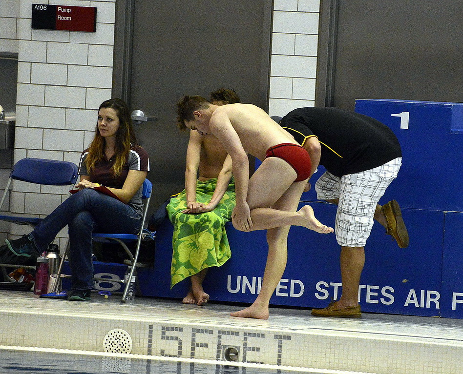 . Loveland diver James Greenup mimics the moves of coach Amon McCrary as they discuss a dive during the preliminary rounds Saturday morning at the Air Force Natatorium. Greenup made it back for finals.