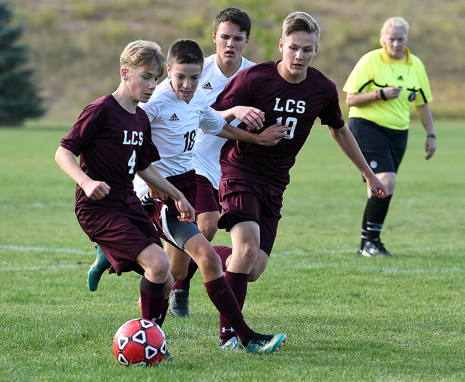 . Loveland Classical\'s Jakob Kuehl takes the ball down field with Andrew McIntyre and Berthoud\'s Bryant Root close by during their soccer game Tuesday, Sept. 4, 2018, at Mehafey Park in Loveland. (Photo by Jenny Sparks/Loveland Reporter-Herald)