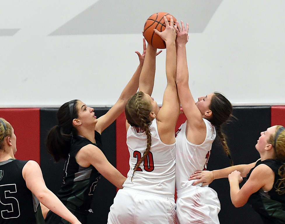 . Loveland High\'s #20 Hannah Sollin and #23 Morgan Driscoll go up for a rebound with Fossil Ridge\'s #24 Kaylee Menefee during their game Tuesday, Jan. 10, 2017, at Loveland High School. (Photo by Jenny Sparks/Loveland Reporter-Herald)