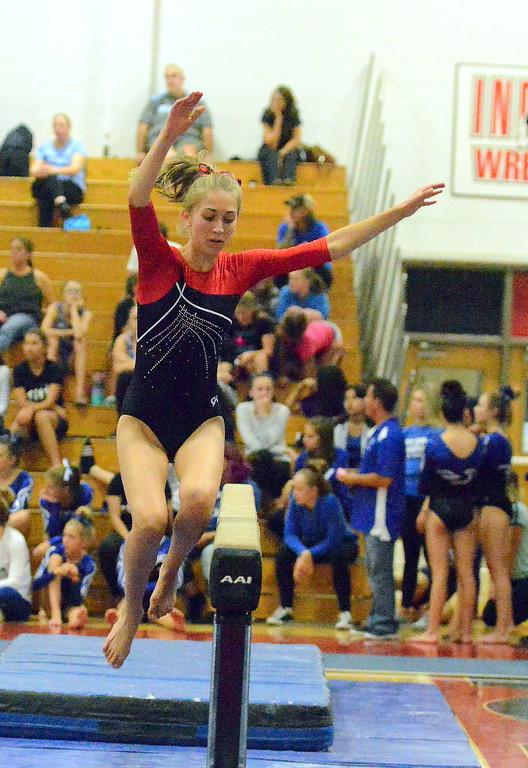 . Loveland\'s Hannah White jumps onto the balance beam at the Loveland Invitational gymnastics meet Friday at LHS. (Mike Brohard/Loveland Reporter-Herald)