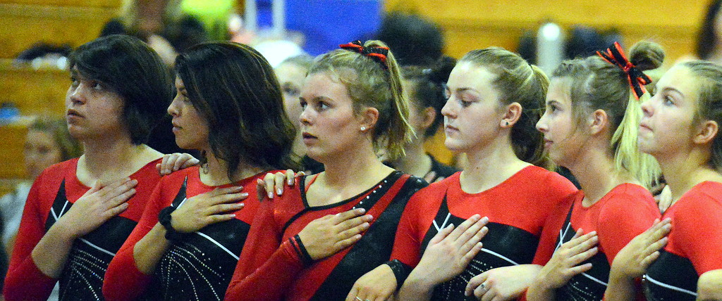 . Loveland\'s gymnasts stand at attention as teammate Lauren Alexander sings the National Anthem before the Loveland Invitational gymnastics meet Friday at LHS. (Mike Brohard/Loveland Reporter-Herald)