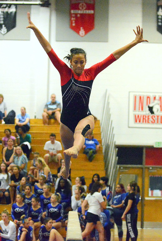 . Kiarra Lapp leaps while performing on the balance beam at the Loveland Invitational gymnastics meet Friday at LHS. (Mike Brohard/Loveland Reporter-Herald)