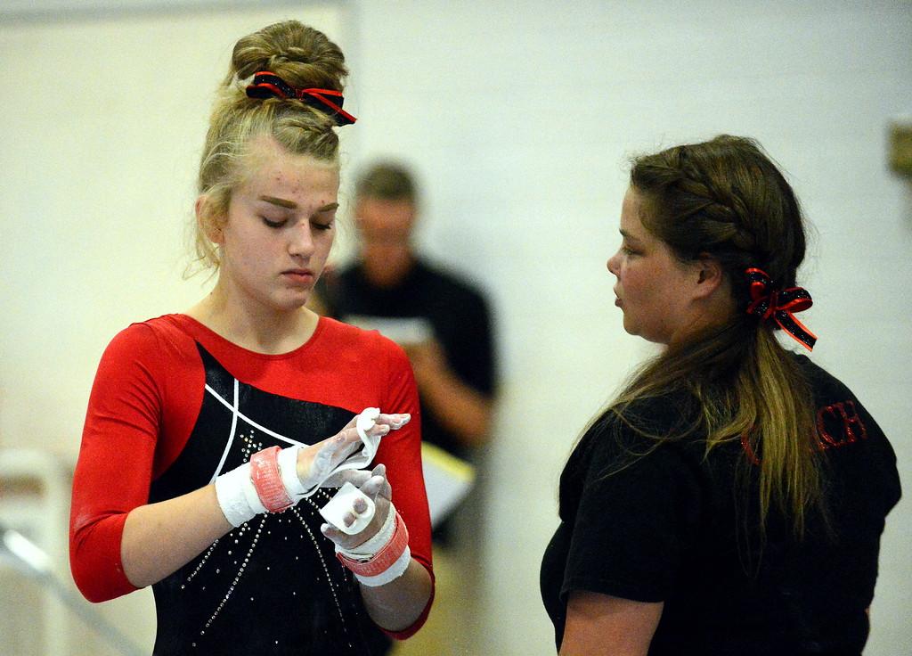 . Loveland coach Jessica Toomey talks to Lauren Alexander before her uneven bars set at the Loveland Invitational gymnastics meet Friday at LHS. (Mike Brohard/Loveland Reporter-Herald)