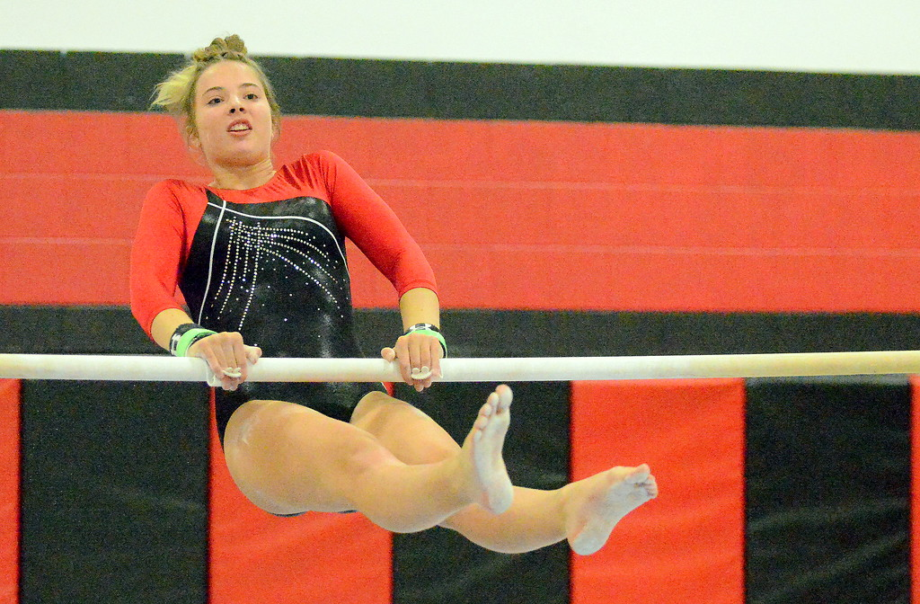 . Loveland\'s Katie Smith competes on the uneven bars at the Loveland Invitational gymnastics meet Friday at LHS. (Mike Brohard/Loveland Reporter-Herald)