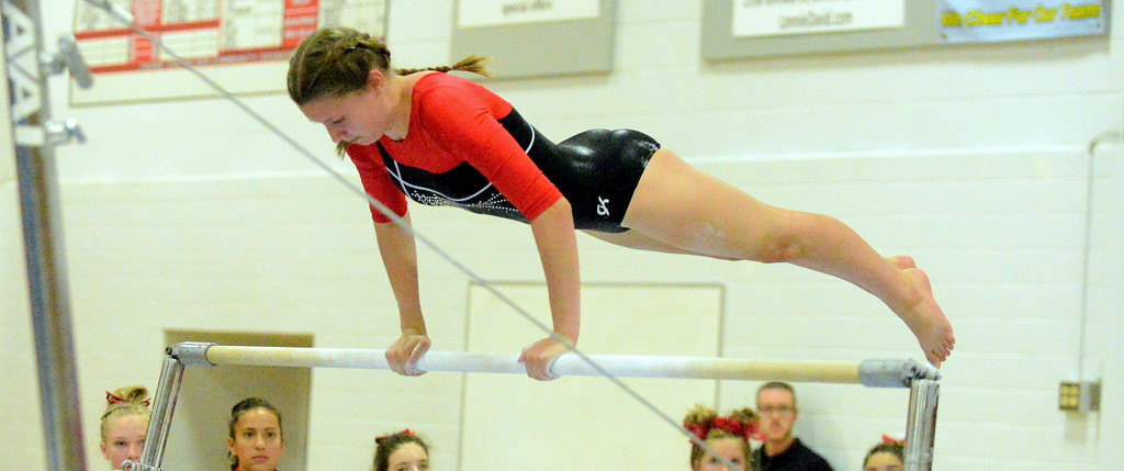 . Loveland\'s Halle White performs on the uneven bars at the Loveland Invitational gymnastics meet Friday at LHS. (Mike Brohard/Loveland Reporter-Herald)