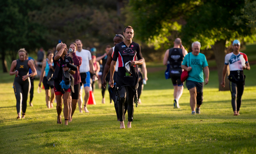 . Participants and their supporters, including Randy Mast, center, from Denver, make their way to the starting point on Lake Loveland Saturday morning June 25, 2016 for the Loveland Lake to Lake Triathlon at North Lake Park. (Photo by Michael Brian/Loveland Reporter-Herald)