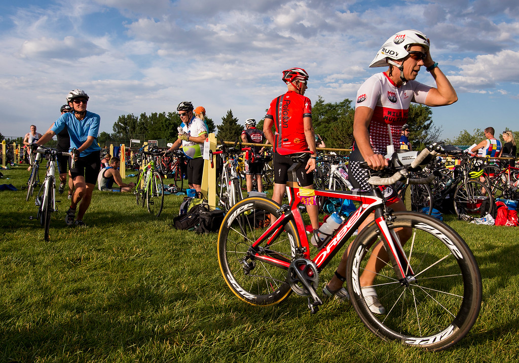 . Kathy Alfino, from Highlands Ranch, adjusts her helmet as she heads out for a 30-mile bike ride during the Loveland Lake to Lake Triathlon Saturday morning June 25, 2016 at North Lake Park. (Photo by Michael Brian/Loveland Reporter-Herald)