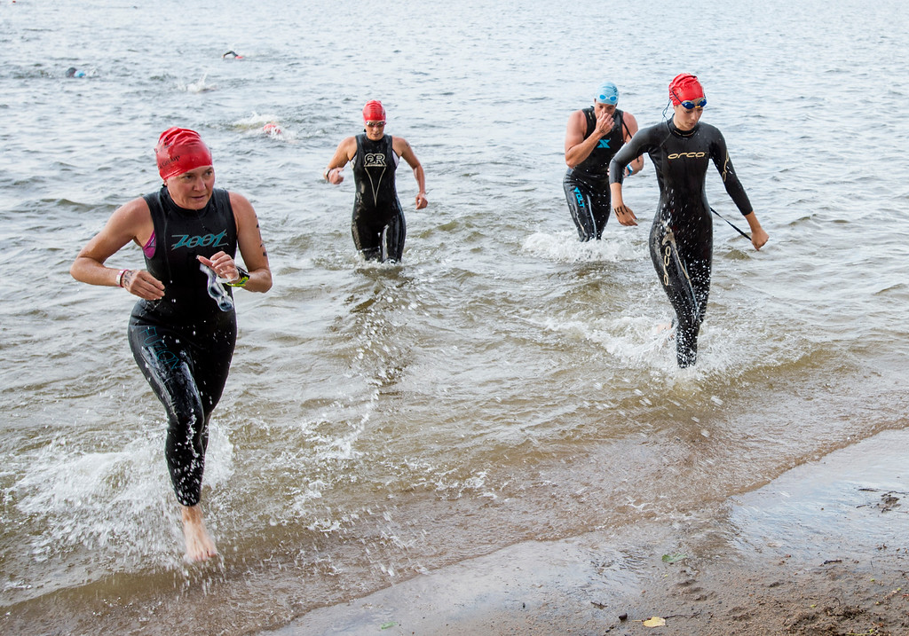 . Participants including Amy Mosser Romero, left, and Savanna Liedy, right, leave the water Saturday morning June 25, 2016  during the Loveland Lake to Lake Triathlon at North Lake Park. (Photo by Michael Brian/Loveland Reporter-Herald)