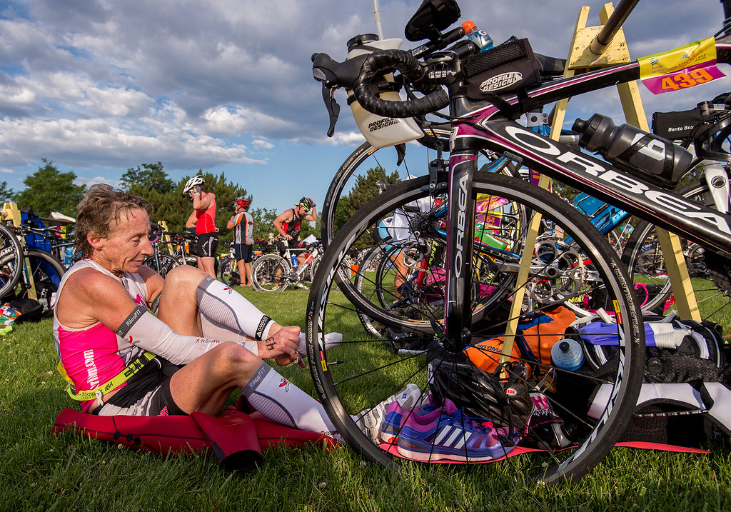 . Kathy Hull puts her socks and shoes on in the bicycle transition area during the Loveland Lake to Lake Triathlon Saturday morning June 25, 2016 at North Lake Park. (Photo by Michael Brian/Loveland Reporter-Herald)