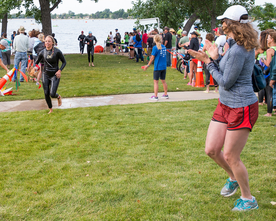 . Ann West, right, cheers for her friend Danielle Polansky, left, during the Loveland Lake to Lake Triathlon Saturday morning June 25, 2016 at North Lake Park. (Photo by Michael Brian/Loveland Reporter-Herald)