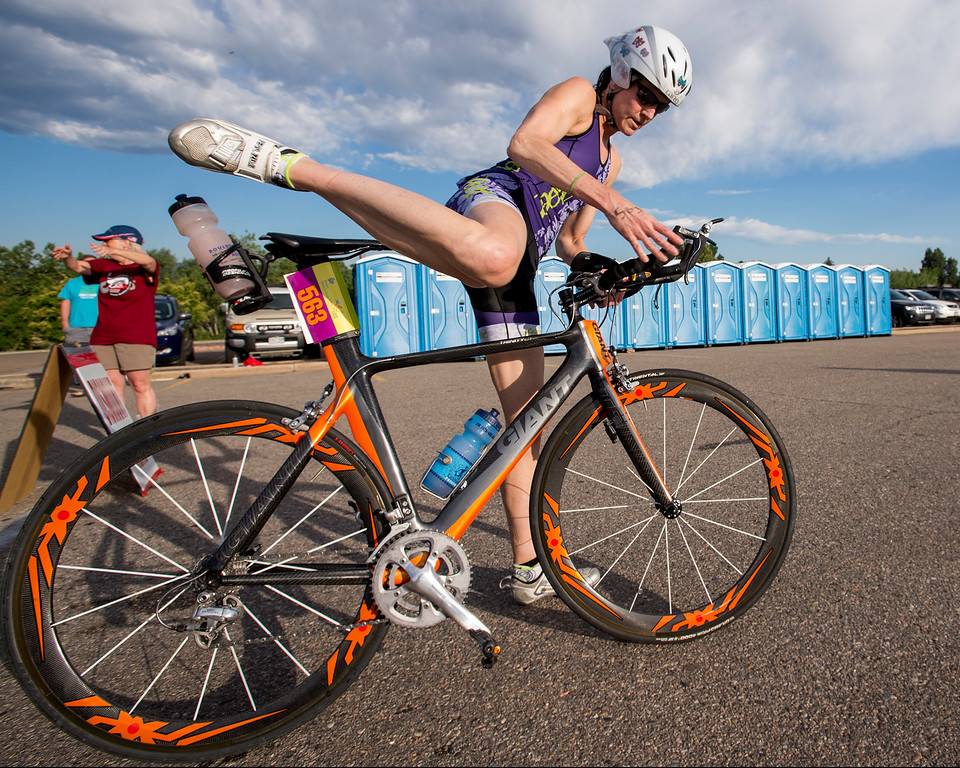 . Eliza Graham, from Denver, mounts her bicycle during the Loveland Lake to Lake Triathlon Saturday morning June 25, 2016 at North Lake Park. (Photo by Michael Brian/Loveland Reporter-Herald)