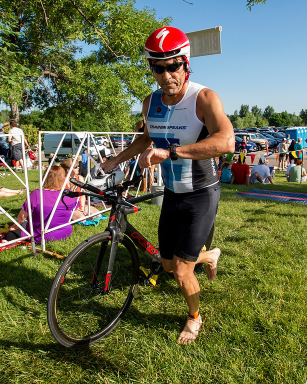 . Alex Flores returns to the bicycle transition area during the Loveland Lake to Lake Triathlon Saturday morning June 25, 2016 at North Lake Park. (Photo by Michael Brian/Loveland Reporter-Herald)