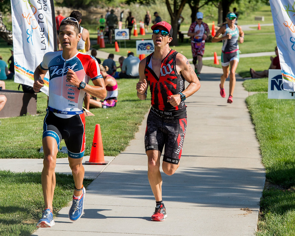 . Colin Laughery, left, and Brandon Wells, right, fight to the finish during the Loveland Lake to Lake Triathlon Saturday morning June 25, 2016 at North Lake Park. (Photo by Michael Brian/Loveland Reporter-Herald)