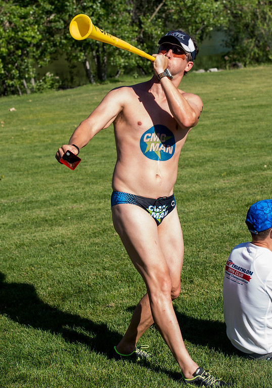 . Tony Rigdon, with the Columbia Multisport Club, a triathlon club based in Columbia, Mo., blows a vuvuzela Saturday morning June 25, 2016 during the Loveland Lake to Lake Triathlon at North Lake Park. Rigdon finished third in his age group. (Photo by Michael Brian/Loveland Reporter-Herald)