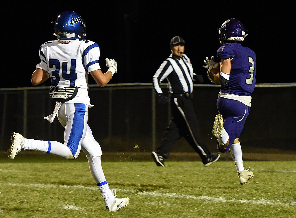 . Mountain View\'s Josiah Baptista catches a touchdown pass as Longmont\'s Jason Murillo tries to catch up during their game Thursday, Oct. 25, 2018, at Patterson Stadium in Loveland.  (Photo by Jenny Sparks/Loveland Reporter-Herald)