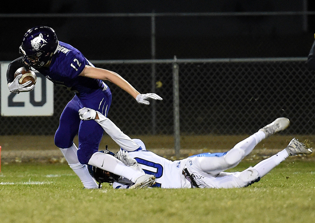 . Mountain View\'s CJ Bever tries to escape Longmont\'s Christian Ramirez  during their game Thursday, Oct. 25, 2018, at Patterson Stadium in Loveland.  (Photo by Jenny Sparks/Loveland Reporter-Herald)
