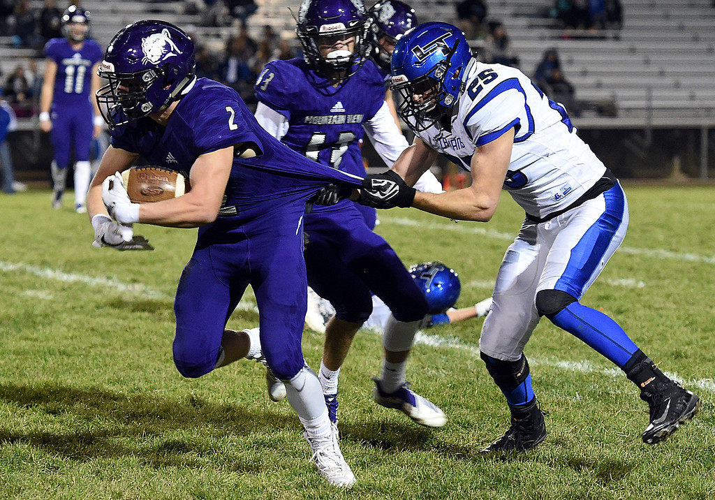 . Mountain View\'s Shane Rasico takes the ball down field as Longmont\'s Matt Sprecher tries to tackle him during their game Thursday, Oct. 25, 2018, at Patterson Stadium in Loveland.  (Photo by Jenny Sparks/Loveland Reporter-Herald)