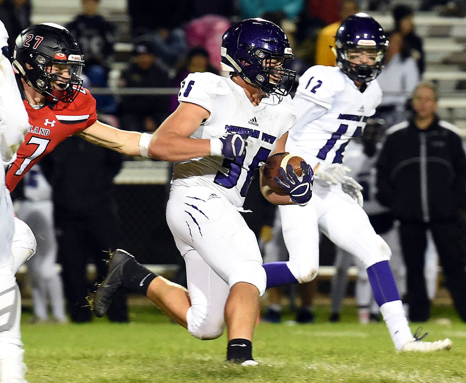 . Mountain View\'s (36) Tobin Armstrong takes the ball downfield with Loveland\'s (27) Cody Donovan behind him during their game Friday, Sept. 28, 2018, at Patterson Stadium in Loveland.   (Photo by Jenny Sparks/Loveland Reporter-Herald)