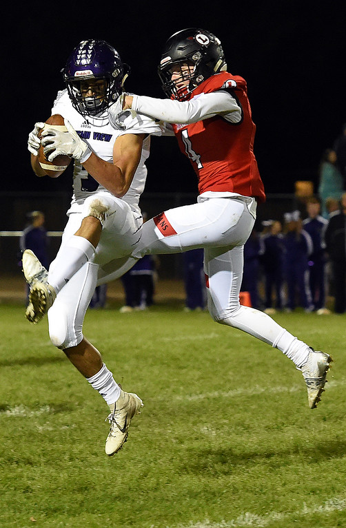 . Mountain View\'s (3) Josiah Baptista catches the ball as Loveland\'s (4) Cody Radowsky tries to block during their game against Friday, Sept. 28, 2018, at Patterson Stadium in Loveland.   (Photo by Jenny Sparks/Loveland Reporter-Herald)