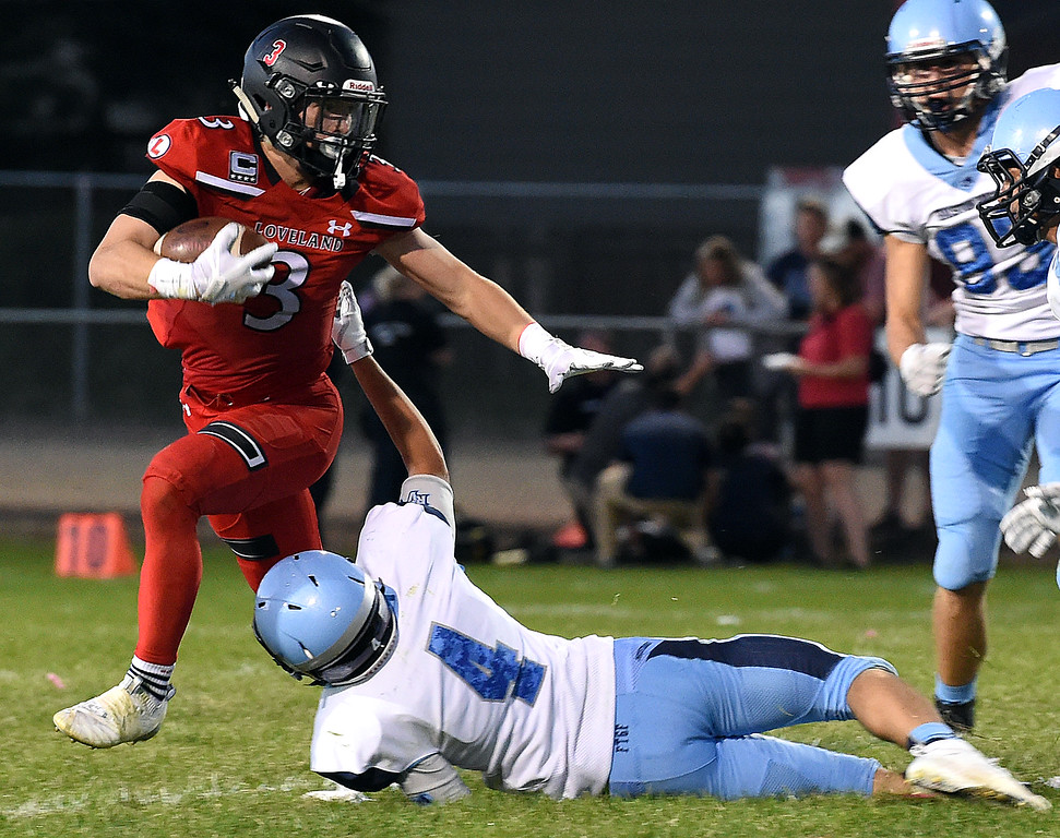 . Loveland\'s (3) Zach Weinmaster escapes tackle by Ralston Valley\'s (4) Kaleb Tischler during their game Wednesday, Sept. 12, 2018, at Patterson Stadium in Loveland.   (Photo by Jenny Sparks/Loveland Reporter-Herald)