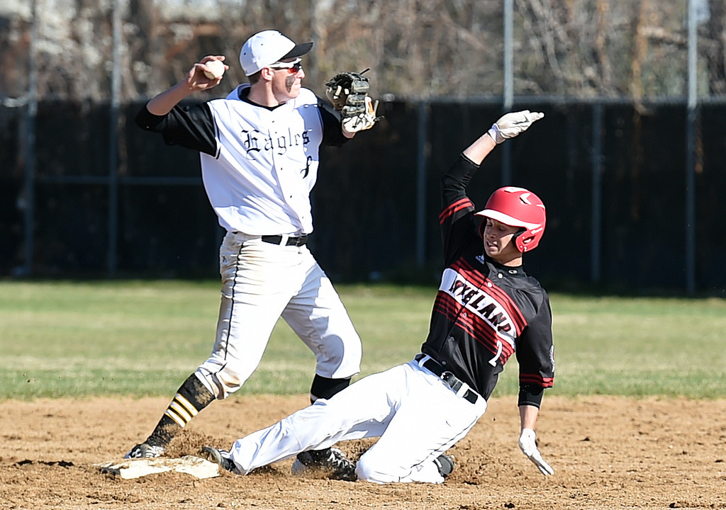 . Loveland\'s #2 Drew Massey slides into second base as Thompson Valley\'s #8 Austin Sobraske throws back to first after taggin him out during their game Wednesday, April 5, 2017, at Thompson Valley High School in Loveland. (Photo by Jenny Sparks/Loveland Reporter-Herald)