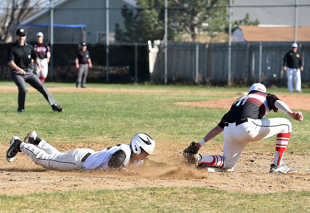 . Thompson Valley\'s #24 Adrian Nava slides into third base as  Loveland\'s #11 Chris Vaccarella tries to tag him out during their game Wednesday, April 5, 2017, at Thompson Valley high School in Loveland. (Photo by Jenny Sparks/Loveland Reporter-Herald) L11 t24