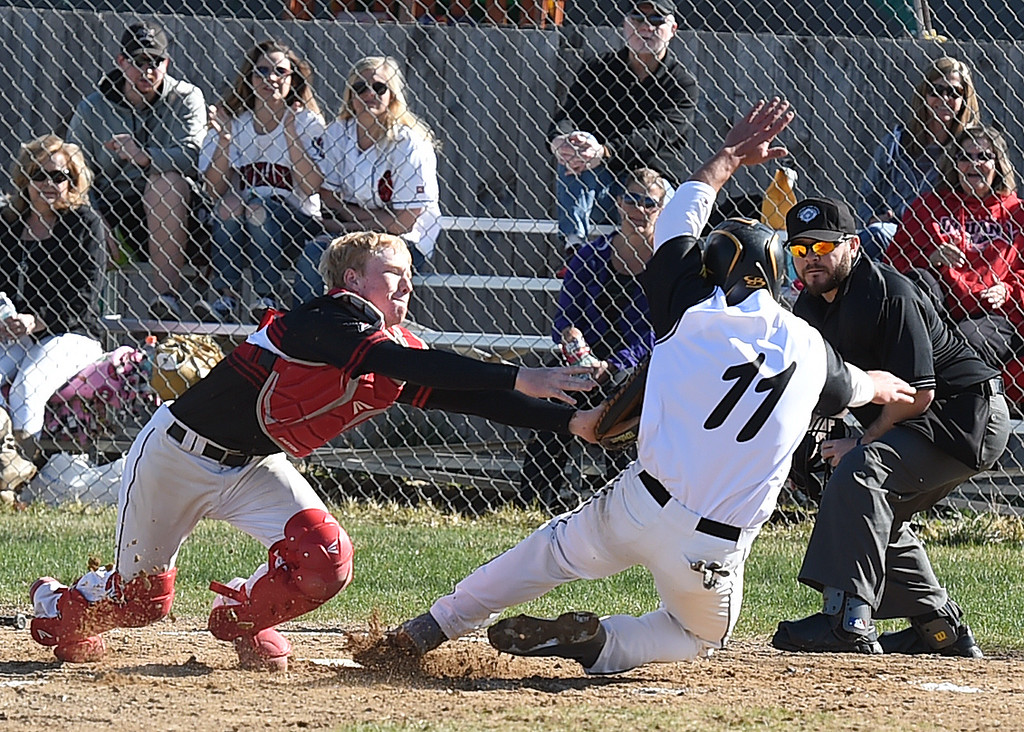. Thompson Valley\'s #11 Mike Berg slides into home as Loveland\'s catcher #3 Ian Myers tags him out during their game Wednesday, April 5, 2017, at Thompson Valley high School in Loveland. (Photo by Jenny Sparks/Loveland Reporter-Herald)