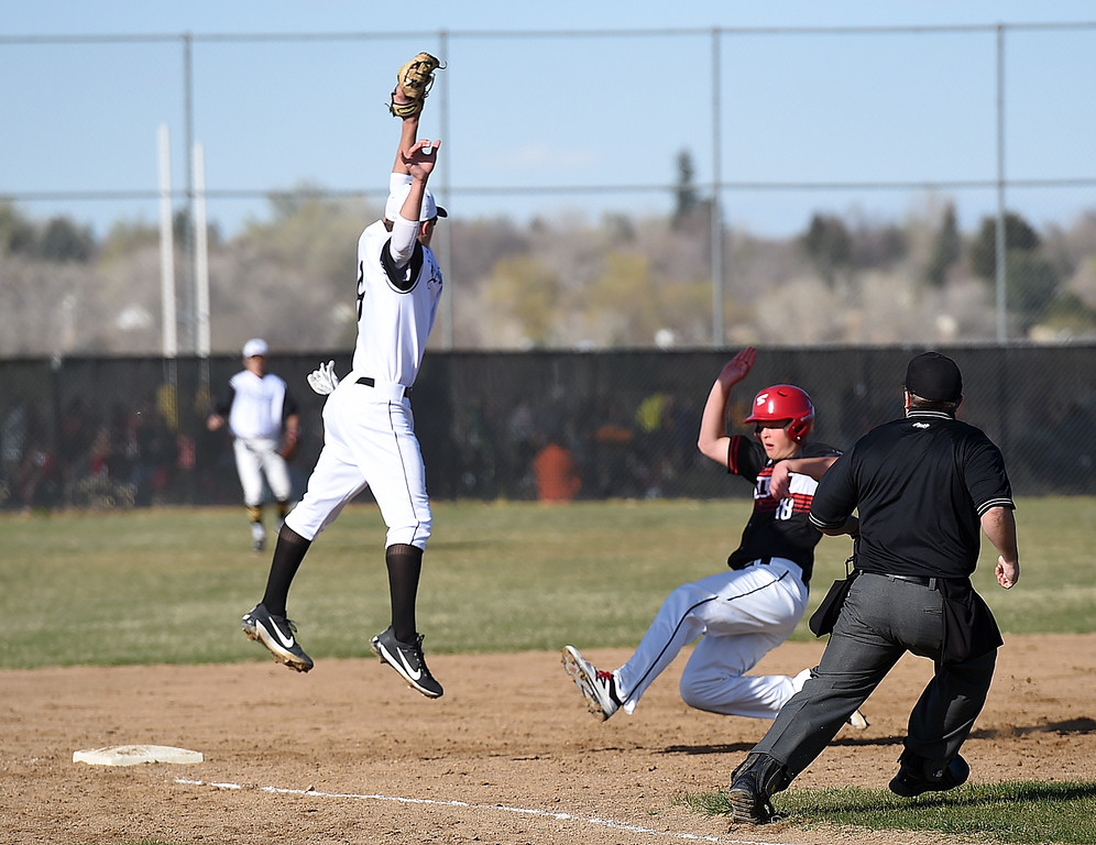 . Loveland\'s #18 Sam Olson jumps up to catch the ball as Thompson Valley\'s #4 Cameron Nellor slides into third base during their game Wednesday, April 5, 2017, at Thompson Valley High School in Loveland. (Photo by Jenny Sparks/Loveland Reporter-Herald)