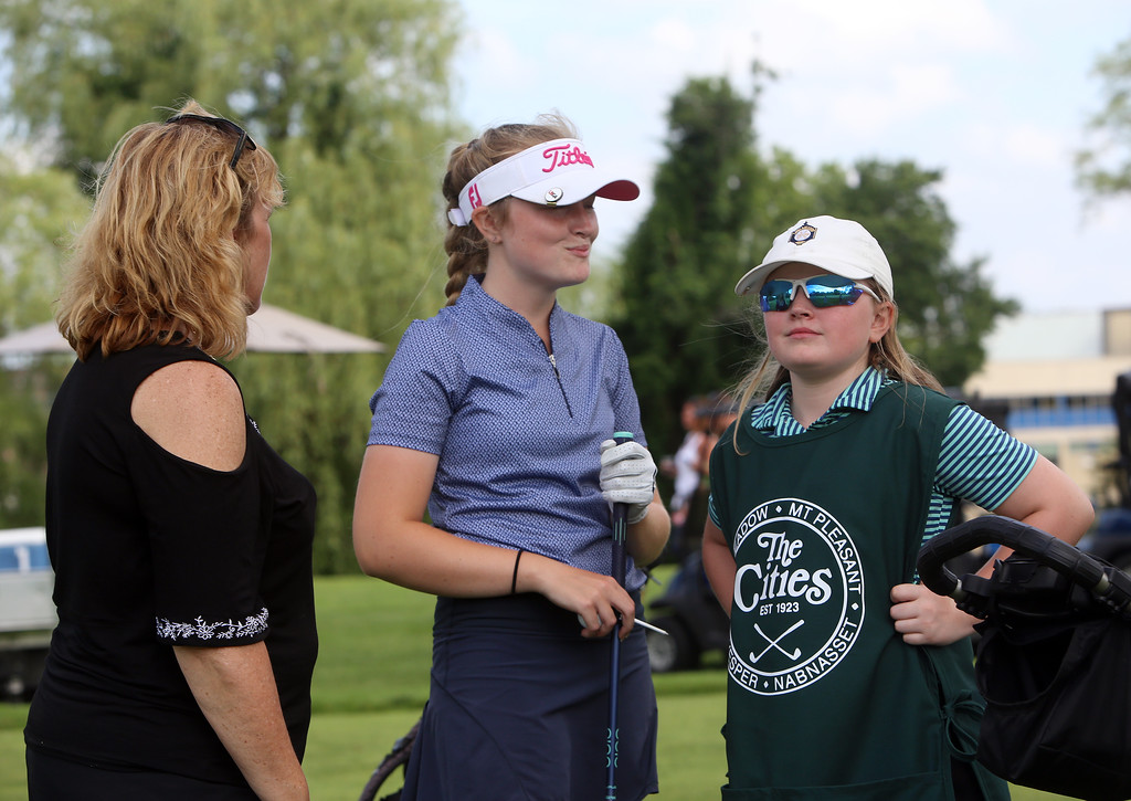 . Lowell City Golf Tournament first round. Morgan Smith, believed to be the first female to qualify for the Lowell City Tournament, with her caddie, younger sister Madison, and mother Lynn Smith, waits to tee off at the 13th hole. (SUN/Julia Malakie)