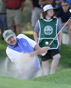 Final round of Lowell City Golf Tournament at Mt Pleasant Golf Club. Phil Smith hits out of a bunker on the 14th hole, and still got a birdie on the hole. At rear is his daughter and caddy, Molly Smith. (SUN/Julia Malakie)