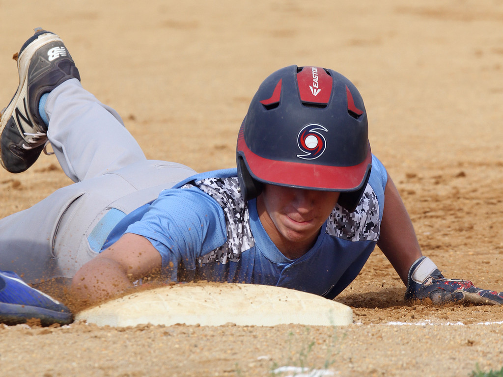 . Lowell vs Dracut 14-15 year old Pony League baseball. Dracut\'s Collin Arsenault (14) dives back safely to first in the top of the first inning. (SUN/Julia Malakie)
