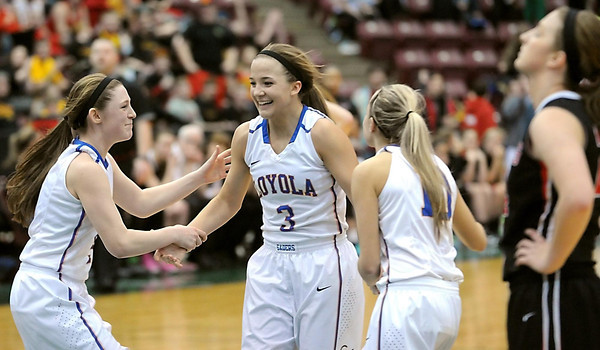 Loyola's Lindsey Theuninck is congratulated by teammates after making the first of two free throws to put the Crusaders ahead with .4 seconds left in overtime Thursday. Pat Christman