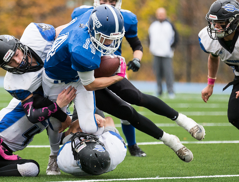 Lunenburg's Benjamin Cumming plows through 3 Murdock defenders while carrying the ball.