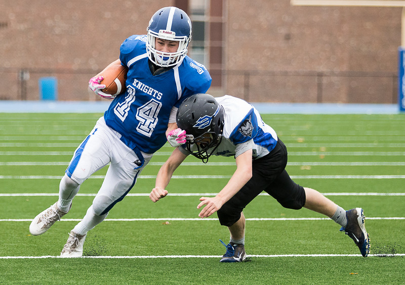 Lunenburg's Benjamin Cumming while carrying the ball is pursued by a Murdock defender.