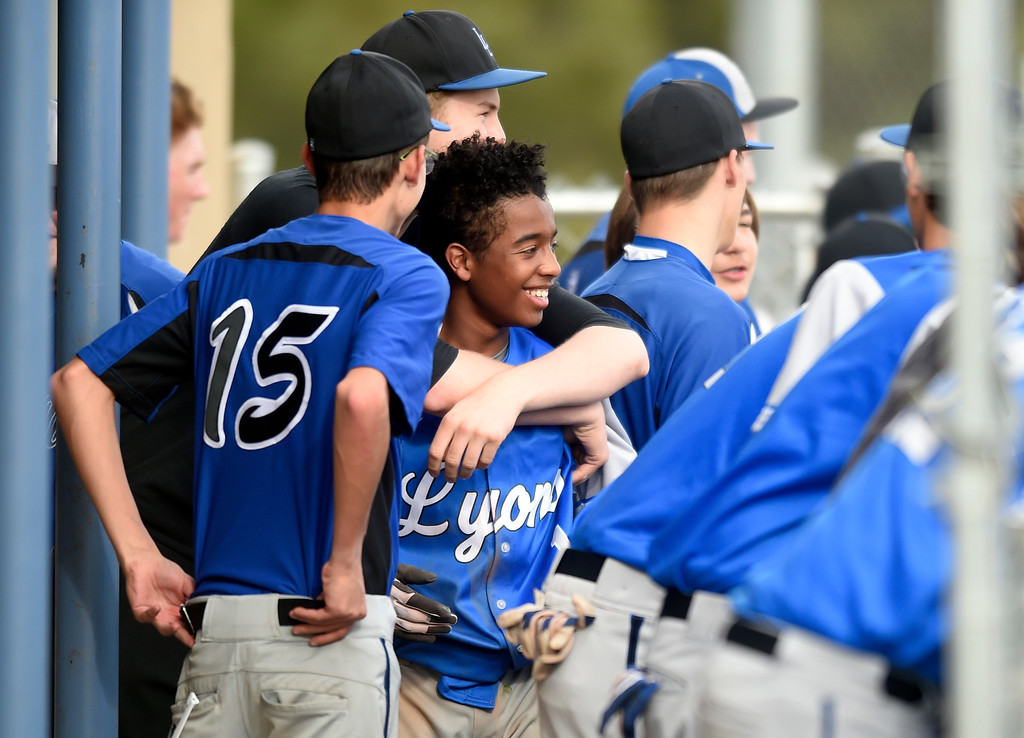 . Lyons High School\'s Aiden Christenson, at center, is congratulated by teammates after scoring a run during a game against Alexander Dawson on Monday in Lafayette. More photos: BoCoPreps.com Jeremy Papasso/ Staff Photographer 04/23/2018