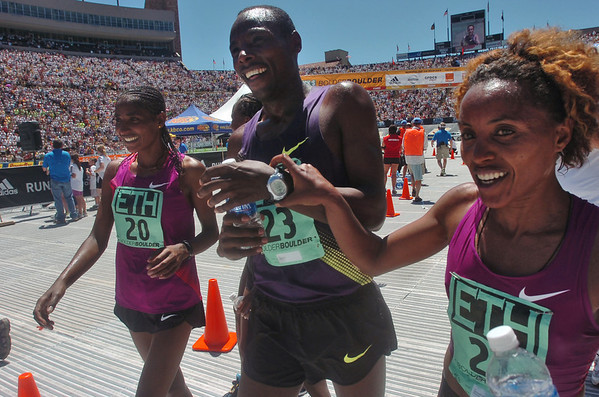 BOLDER<br /> Ethiopia's Tadese Tola, center, celebrates his time at the finish line with compatriots Mamito Daska (winner of the women's race), left, and Belianesh Zemedkun, right, during the 32nd Annual Day Bolder Boulder on Monday. Tola crossed the line hand in hand with both his male teammates.<br /> Photo by Marty Caivano/Camera/May 31, 2010