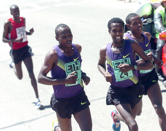 From left to right Tadese Tola #23, Tilahun Regassa #24, and Lelisa Desisa #22, of Ethiopia are chased by Simon Cheprot, #15, of Kenya during the Men's Elite Race of the Bolder Boulder on Monday May 31, 2010<br /> Photo by Paul Aiken / The Camera / May 31, 2010