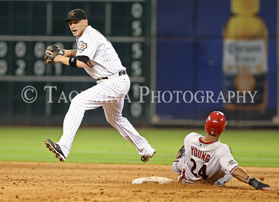 May 27, 2011; Houston, TX, USA; Houston Astros infielder Clint Barmes (12) leaps as Arizona Diamondbacks outfielder Chris Young (24) slides into second base in the ninth inning at Minute Maid Park. Mandatory Credit: Troy Taormina-US PRESSWIRE
