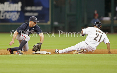 June 13, 2011; Houston, TX, USA; Houston Astros outfielder Michael Bourn (21) slides safely with a stolen base as Atlanta Braves infielder Dan Uggla (left) fields the throw in the fifth inning at Minute Maid Park. Mandatory Credit: Troy Taormina-US PRESSWIRE