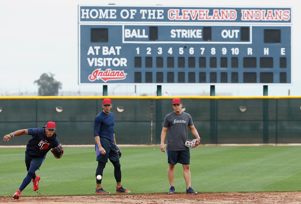 . Cleveland Indians shortstop Francisco Lindor, left, gets set to field a ground ball as second baseman Erik Gonzalez, center, and third baseman Giovanny Urshela, right, look on at the team\'s spring training facility Friday, Feb. 16, 2018, in Goodyear, Ariz. (AP Photo/Ross D. Franklin)