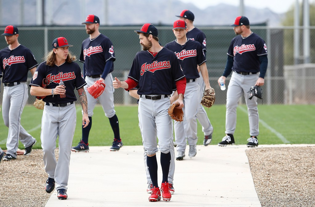 . Cleveland Indians relief pitcher Andrew Miller, right, talks with starting pitcher Mike Clevinger, left, as they walk with pitchers to work out at the Indians spring training facility Friday, Feb. 16, 2018, in Goodyear, Ariz. (AP Photo/Ross D. Franklin)
