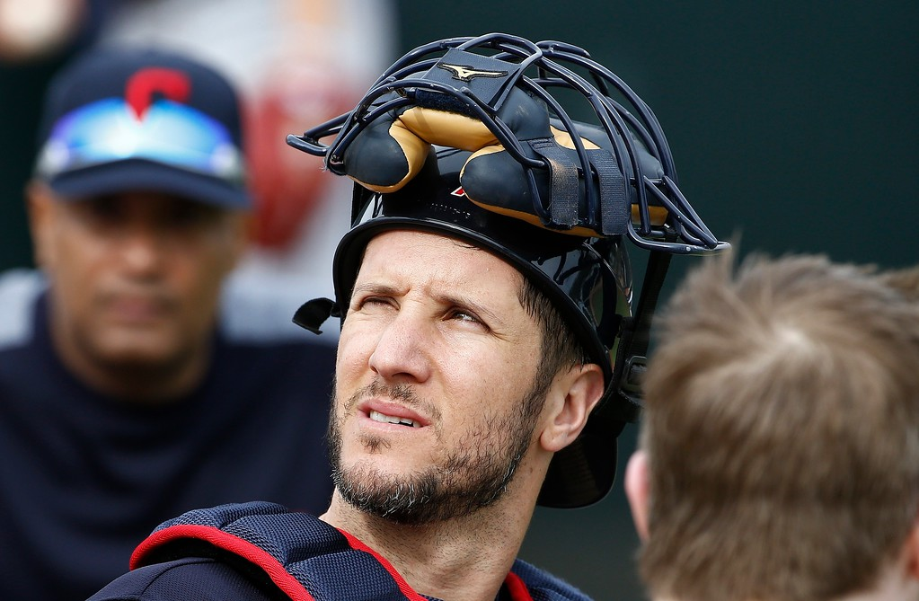 . Cleveland Indians catcher Yan Gomes listens to a coach after Gomes catching session at the Indians spring training facility Friday, Feb. 16, 2018, in Goodyear, Ariz. (AP Photo/Ross D. Franklin)