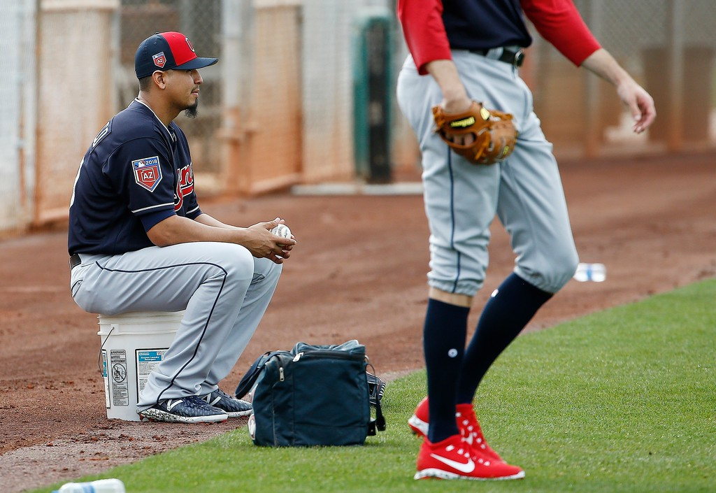 . Cleveland Indians starting pitcher Carlos Carrasco watches teammates warm up at the Indians spring training facility Friday, Feb. 16, 2018, in Goodyear, Ariz. (AP Photo/Ross D. Franklin)