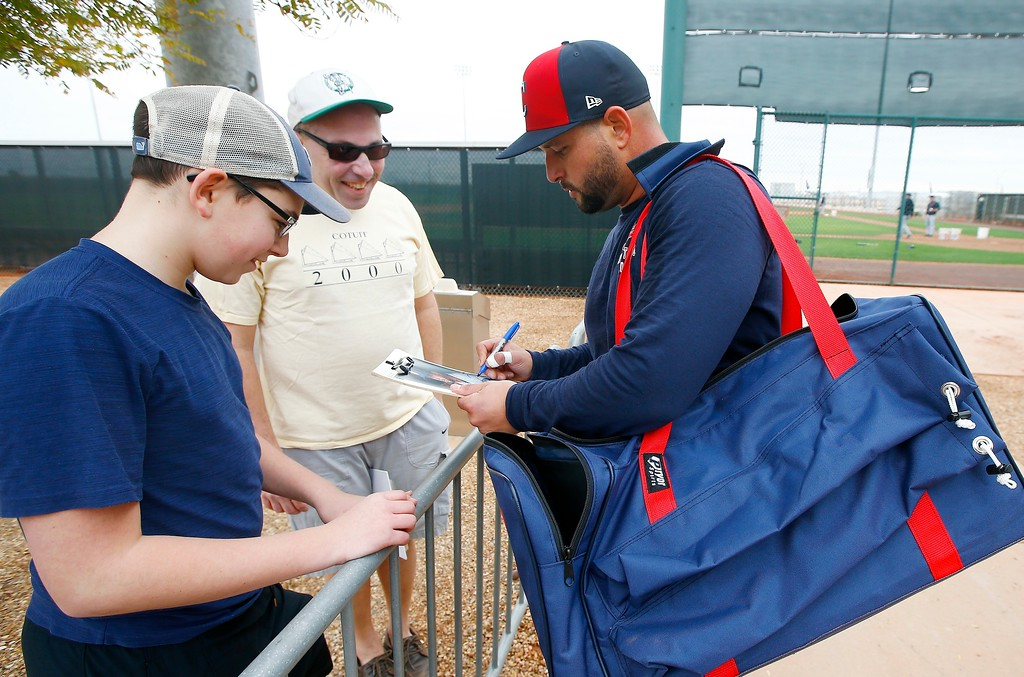 . Cleveland Indians first baseman Yonder Alonso, right, gives an autograph at the team\'s spring training facility Friday, Feb. 16, 2018, in Goodyear, Ariz. (AP Photo/Ross D. Franklin)