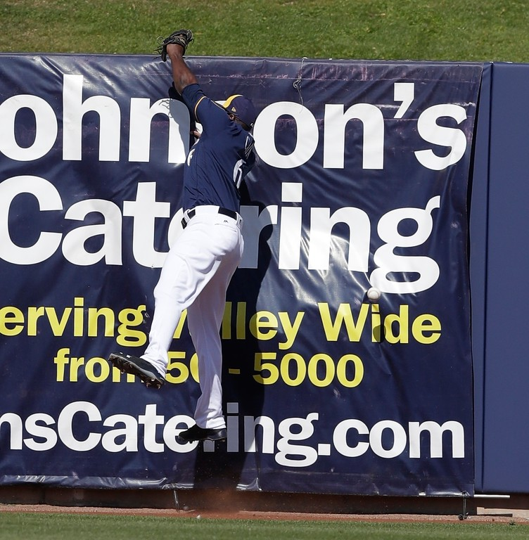 . Milwaukee Brewers outfielder Lorenzo Cain misplays the double hit by Cleveland Indians\' Roberto Perez during the fourth inning of a spring training baseball game, Monday, Feb. 26, 2018, in Maryvale, Ariz. (AP Photo/Carlos Osorio)